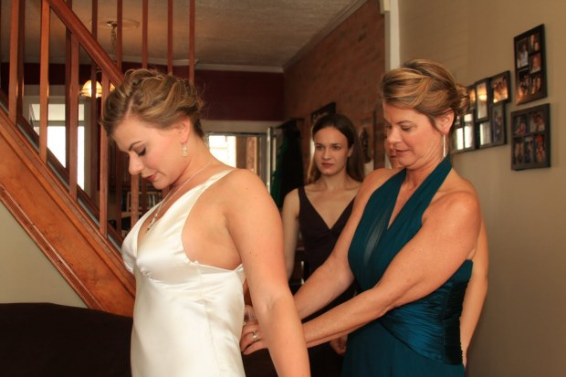 Mom buttoning me into my dress on my wedding day